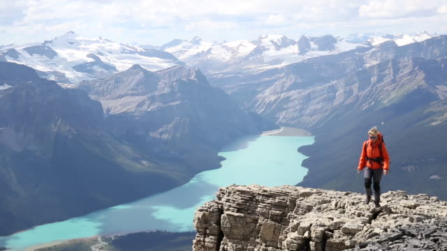 vidéos et rushes de female mountaineer pauses on high promontory above valley, lake - cheveux blonds