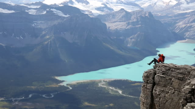 Female mountaineer pauses on high promontory above valley, lake