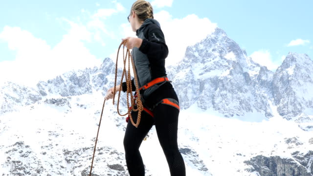 Female mountaineer stands on ledge coiling rope while preparing to belay the next climber