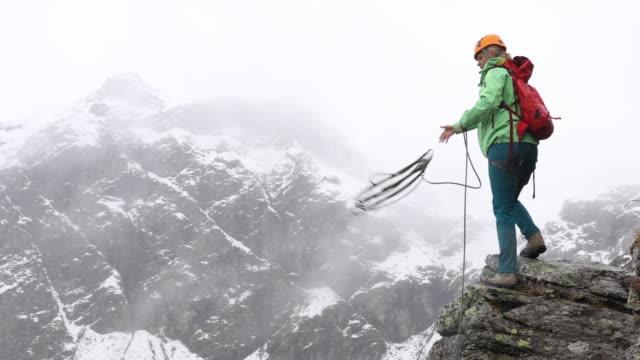 vídeos de stock e filmes b-roll de female mountaineer tosses rope outwards for rappel (abseil) - rapel