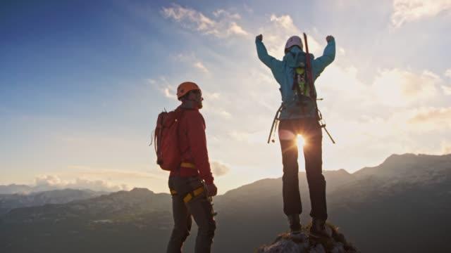 stockvideo's en b-roll-footage met vrouwelijke bergbeklimmers verhogen handen op een bergtop en vieren met collega bergbeklimmer - wandelen buitensport