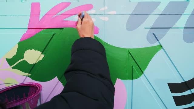 vidéos et rushes de artiste féminin de peinture murale au travail - arts culture et spectacles
