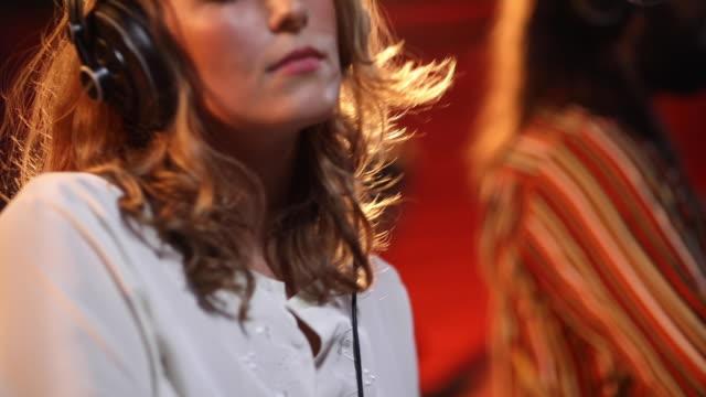 musicista donna che balla e suona il sintetizzatore sul palco con la band - rocking video stock e b–roll