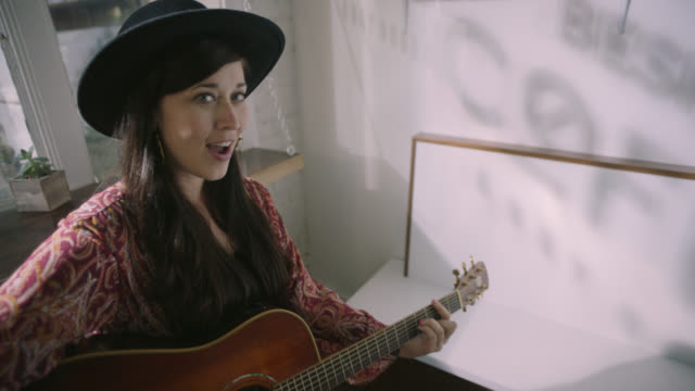 Female musician plays acoustic guitar and sings at camera in downtown city coffee shop.