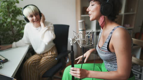 female musician working with her producer in home studio - producer stock videos & royalty-free footage