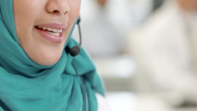 vídeos y material grabado en eventos de stock de tu mujer musulmana operador de centro de llamadas teniendo una llamada - pañuelo de cabeza