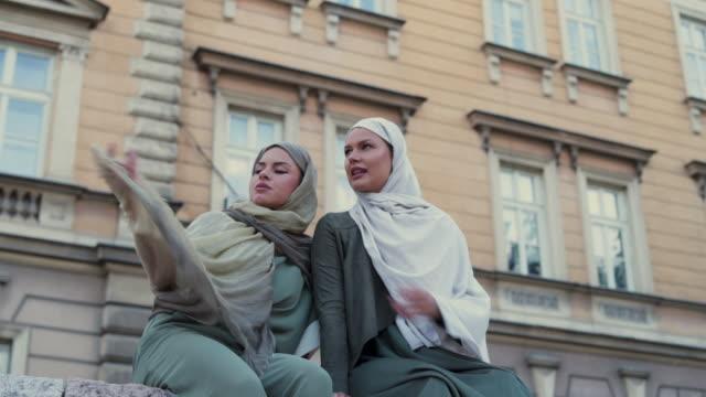 vídeos de stock, filmes e b-roll de femininos amigos muçulmanos, aproveitando o dia - vestuário modesto