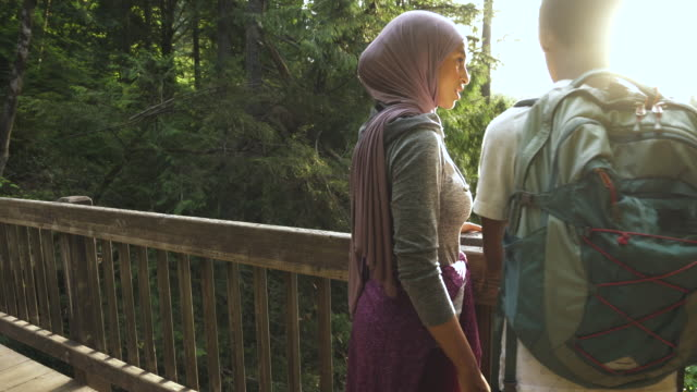 Female muslim hiker and brother admiring the summer evening from a bridge