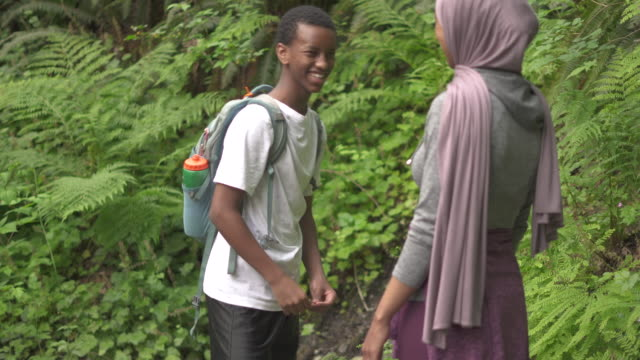 Female muslim hiker playing game with brother during hike on summer evening