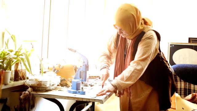女性作業員カティングイスラム教徒のレザーストリップ逆光 - 僧衣点の映像素材/bロール