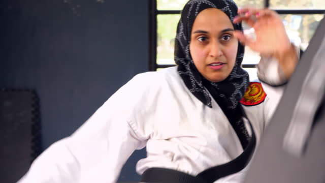 vídeos de stock e filmes b-roll de cu female muslim self defense instructor demonstrating kick during class in gym - artes marciais