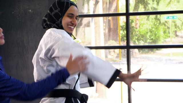 r/f female muslim self defense instructor demonstrating technique during class for women - 武道点の映像素材/bロール