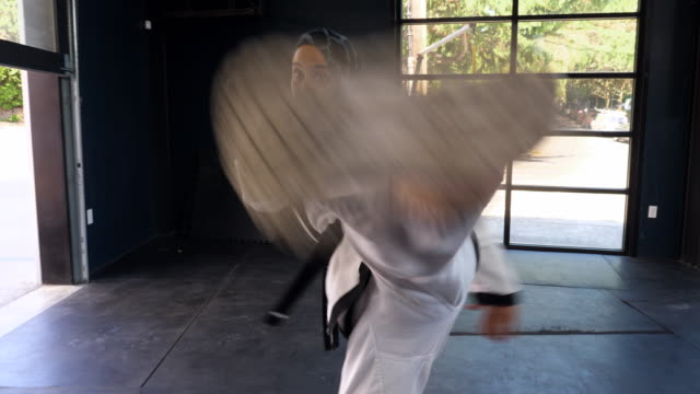 vídeos de stock e filmes b-roll de ts female muslim self defense instructor practicing kick in gym - artes marciais