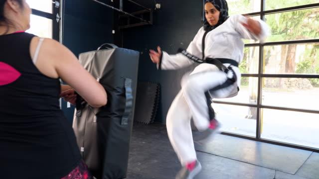 ts female muslim self defense instructor preparing to demonstrate kick during class in gym - islam stock-videos und b-roll-filmmaterial