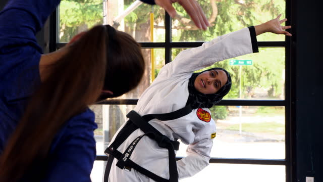 ms female muslim self defense instructor warming up with female students in gym before class - 武道点の映像素材/bロール
