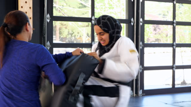 ms female muslim self defense instuctor showing students kicking technique during class in gym - 武道点の映像素材/bロール