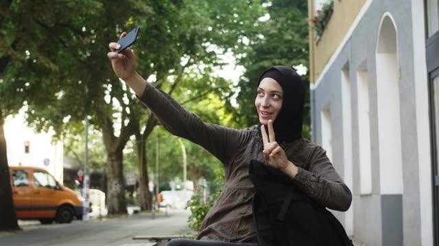 vídeos de stock, filmes e b-roll de feminino viajante muçulmano, tomando um selfie (câmera lenta) - hijab