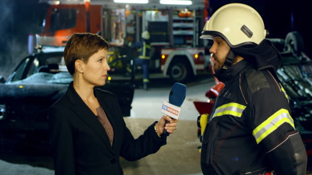 Female news reporter interviewing a male firefighter live at the scene of a car accident at night