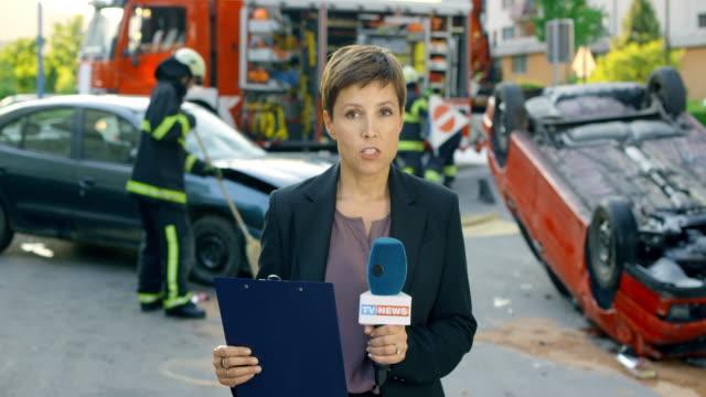 vídeos de stock, filmes e b-roll de femininas notícias repórter relatórios sobre um acidente de carro ao vivo da cena da crime - apresentador de noticiário
