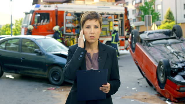 Female news reporter reporting live from the scene of a car accident