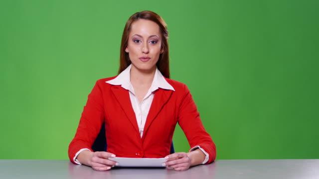 4k weibliche nachrichtensprecher mit roten anzug auf grünem hintergrund - redner stock-videos und b-roll-filmmaterial