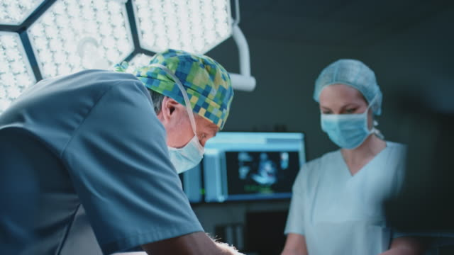 female nurse assisting surgeon during surgery - filmato non girato negli usa video stock e b–roll