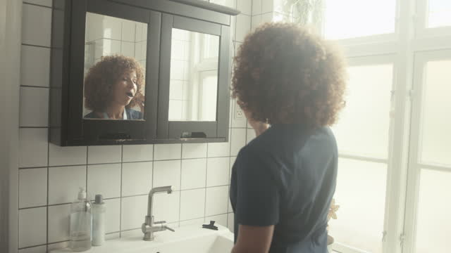female nurse brushing teeth in bathroom - healthcare worker stock videos & royalty-free footage