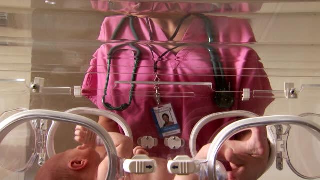Female nurse caressing newborn in incubator