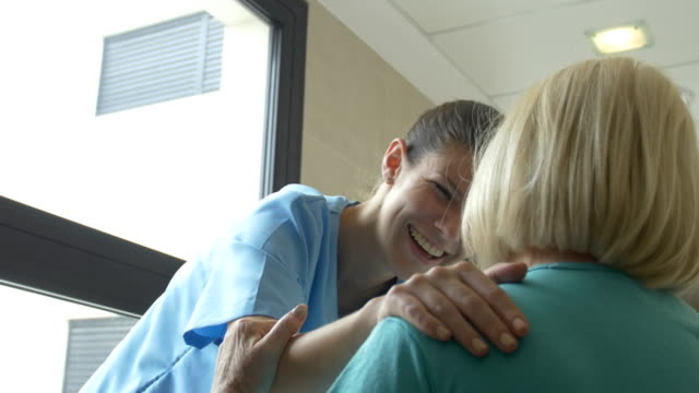 Female nurse communicating with senior woman