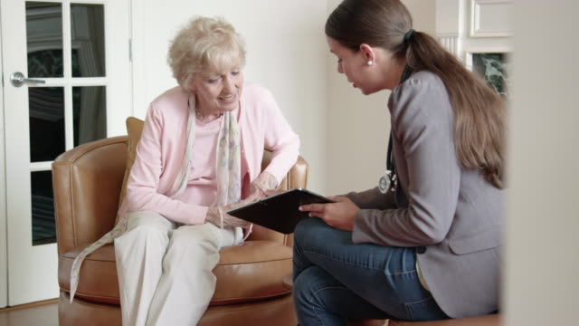 female nurse discusses healthcare with senior woman using a digital tablet - assistance stock videos & royalty-free footage