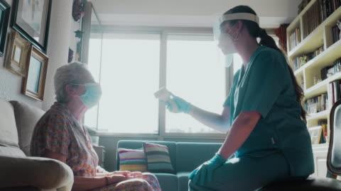 en kvinnlig sjuksköterska gör en temperaturkontroll till en äldre kvinna. - infektionssjukdom bildbanksvideor och videomaterial från bakom kulisserna