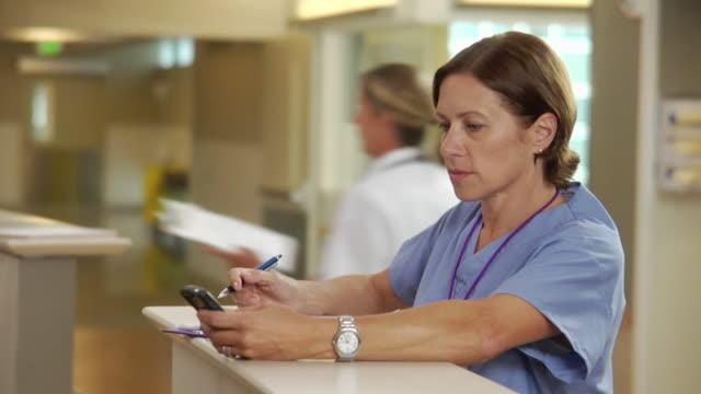vídeos de stock e filmes b-roll de ms selective focus female nurse filling out patient's charts in hospital, doctor in background, seattle, washington, usa - enfermeira