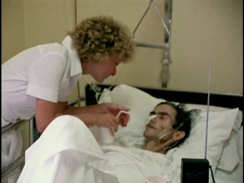 vidéos et rushes de 1978, ms female nurse helping patient to drink, los angeles, california, usa - infirmière