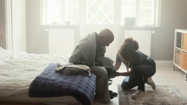 female nurse helping senior man to put shoe - dedication stock videos & royalty-free footage