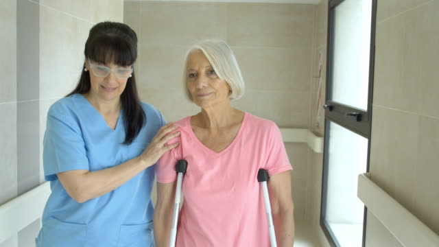 Female nurse helping senior woman on crutches
