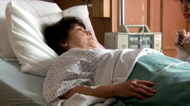 female nurse holding hand of mature woman in hospital - brechreiz stock-videos und b-roll-filmmaterial