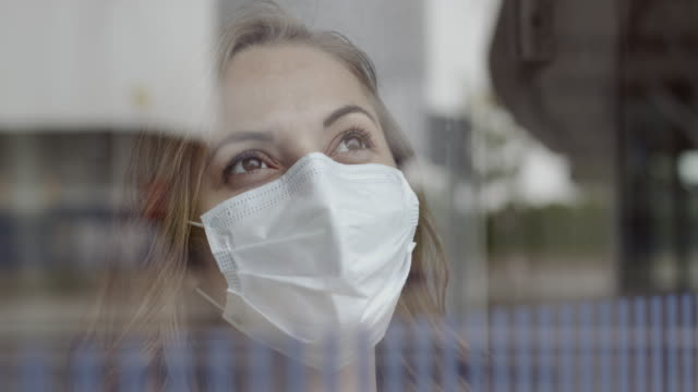 female nurse in hospital wearing protective face mask looking trough window with positive emotion during lockdown covid19 pandemic - endurance stock videos & royalty-free footage