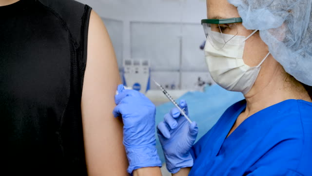 female nurse injecting a vaccine to a male patient - limb body part stock videos & royalty-free footage
