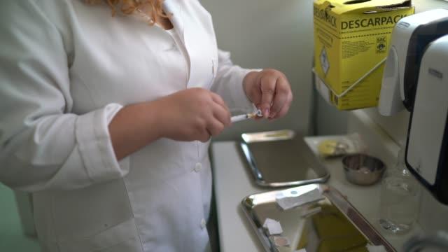 vídeos de stock, filmes e b-roll de enfermeira que prepara vacina - vacina