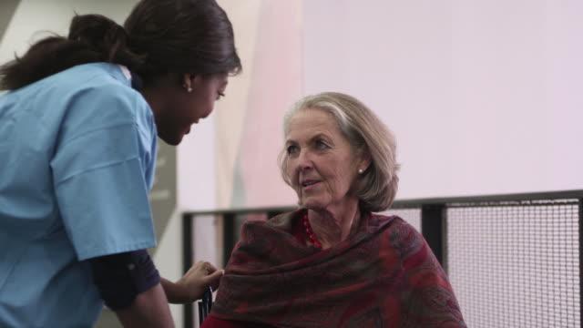 stockvideo's en b-roll-footage met female nurse talking with patient - operatiekleding