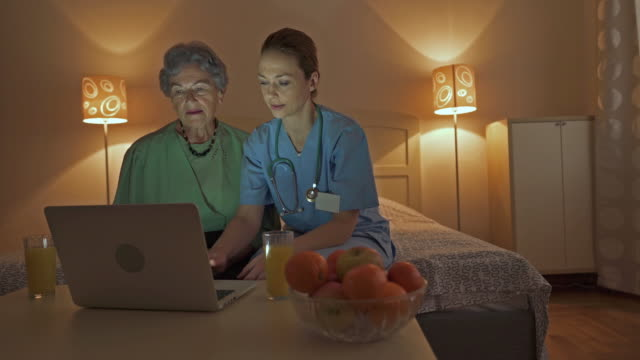 female nurse teaching an old woman how to use laptop at home. - sheltered housing stock videos & royalty-free footage