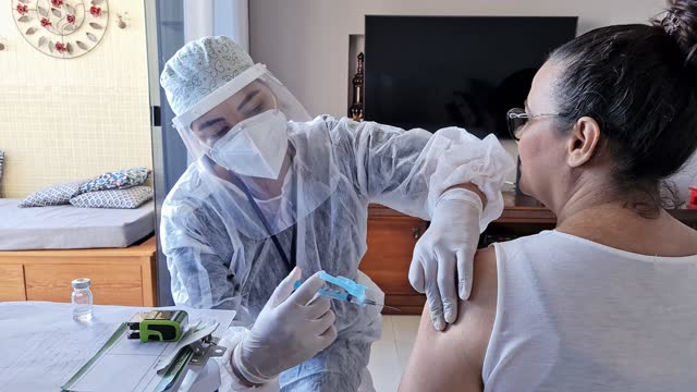 female nurse vaccinating a mature woman at home - pardo brazilian stock videos & royalty-free footage