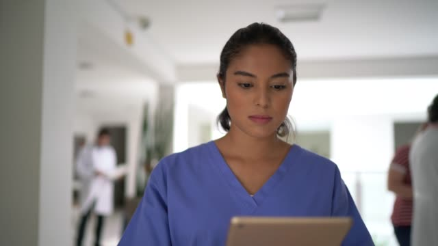 female nurse walking and using tablet at hospital - nurse walking stock videos & royalty-free footage