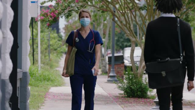vídeos y material grabado en eventos de stock de female nurse walks down sidewalk looking at phone, enters building - trabajador de primera línea