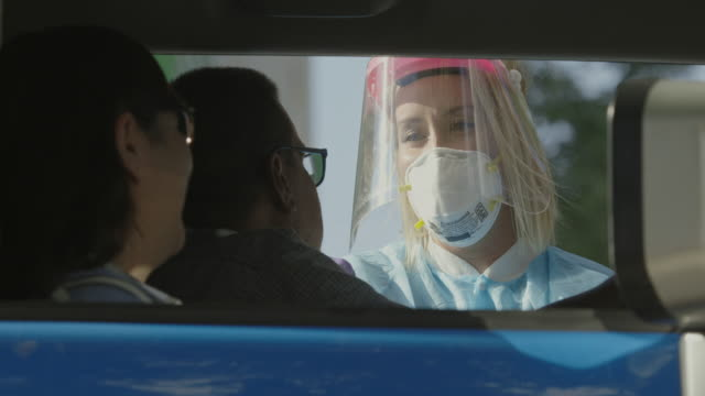 a female nurse wearing a gown, a surgical face mask, and a face shield talks to a hispanic couple in their car as she swabs the man's nose with a cotton swab in a drive-up (drive through) covid-19 (coronavirus) testing line outside a medical clinic/hospit - medical occupation stock videos & royalty-free footage