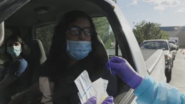 a female nurse wearing a gown, a surgical face mask, gloves, and a face shield walks up to a male person of color and a female sitting in his car and explains cotton swab testing in a drive-up (drive through) covid-19 (coronavirus) testing line outside a - test drive stock videos & royalty-free footage