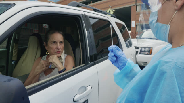 a female nurse wearing a gown, surgical face mask, gloves, and a face shield hands a testing swab to a masked woman in her seventies in a white suv in a drive-up covid-19 testing line outside a medical clinic/hospital outdoors - test drive stock videos & royalty-free footage