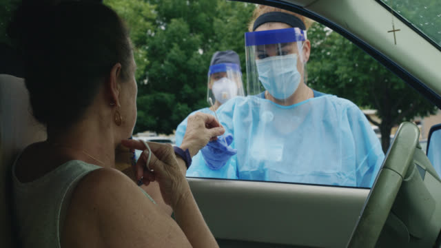 a female nurse wearing a gown, surgical face mask, gloves, and a face shield hands a testing swab to a masked woman in her seventies in a white suv in a drive-up covid-19 testing line outside a medical clinic/hospital outdoors - esame video stock e b–roll