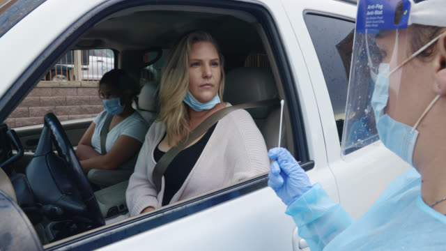 a female nurse wearing a gown, surgical face mask, gloves, and a face shield talks to a woman in her thirties sitting in her car about testing while holding a cotton swab in a drive-up covid-19 testing line outside a medical clinic/hospital outdoors - coronavirus stock videos & royalty-free footage