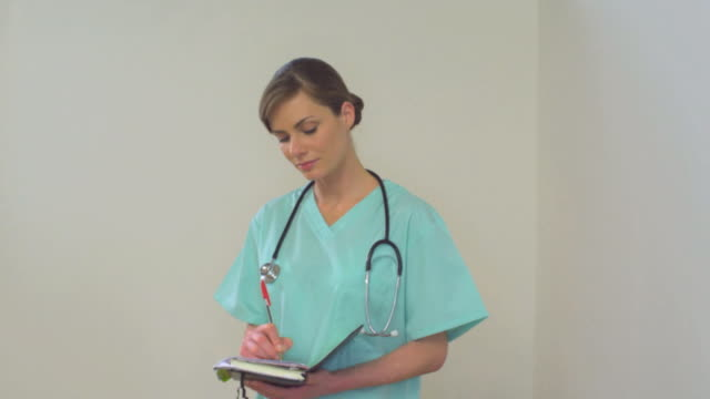 ms slo mo female nurse wearing scrub and taking notes / london, greater london, united kingdom   - einzelne frau über 30 stock-videos und b-roll-filmmaterial